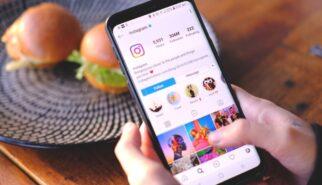 Pessoa com o celular na mão acessando o aplicativo instagram.